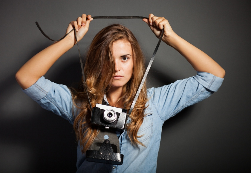 Sexy photographer in jeans shirt with old camera